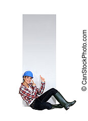 Female builder sat by blank poster