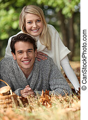 a young couple lying down on the grass, a mushrooms basket...