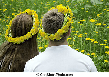 Loving couple in wreaths from dandelions on a background of field with flowers