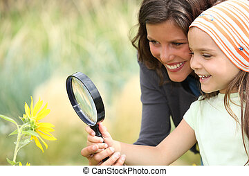 Mother and daughter examining a flower using a magnifying...