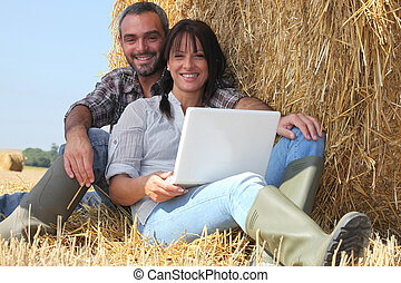 Couple relaxing with laptop in straw