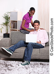Casual couple using a laptop at home