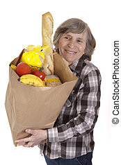 senior carrying a bag of groceries - senior woman with a bag...