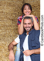 Farmer couple sitting amongst hay bales