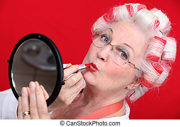 senior woman with curlers in her hair putting lipstick