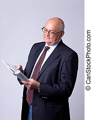 portrait of a successful senior man with book on gray...