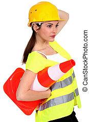 A traffic controller carrying a pylon