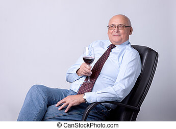 portrait of a successful senior man with glass of wine on...