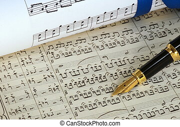 composition - rolled sheet music and a fountain pen over a...