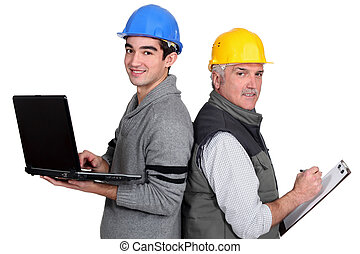 senior plumber and junior standing back to back with laptop...