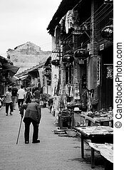 An old woman walking along the street - CHINA - MAY 17, An...