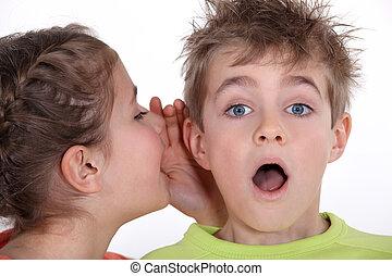 little girl telling a boy a secret