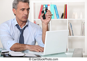 Man squeezing hand grippers while reading an e-mail