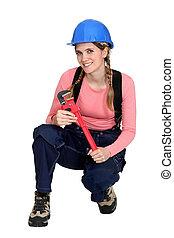A kneeling female construction worker.
