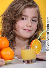 Portrait of an adorable girl drinking a glass of orange juice