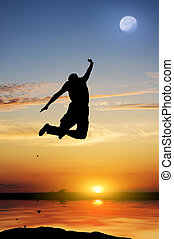 Silhouette of the person jumping on a decline