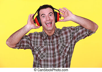 happy man wearing earmuffs cancelling noise