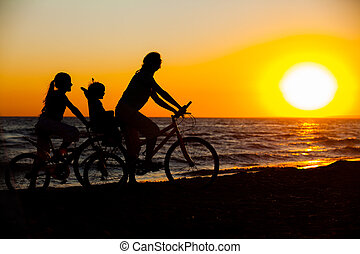 Mother and her kids on the bicycle silhouettes