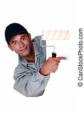 Tradesman holding a paint roller and pointing to a blank...
