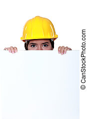 A female construction worker hiding behind a billboard.