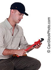 Confused man looking at a pipe wrench