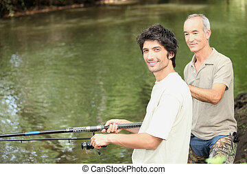 an old man and a young man angling beside a river