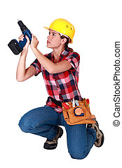 Woman carpenter using screwdriver