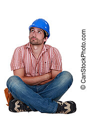 craftsman sitting cross-legged and thinking