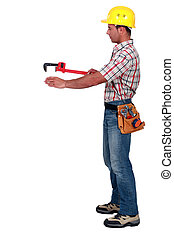 Tradesman using a pipe wrench to help drag and place an...