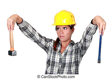 Apprehensive tradeswoman holding a hammer and chisel