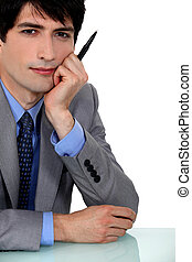 portrait of young businessman with face resting on hand