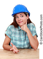 Thoughtful woman in a hardhat sitting at a desk