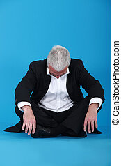 Grey-haired businessman taking nap