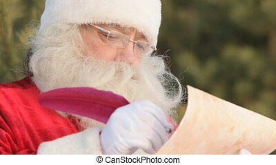 Writing Christmas letter - Close-up of Santa Claus writing a...