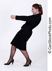 Businesswoman pulling an invisible object