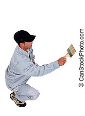 Squatting tradesman painting a wall