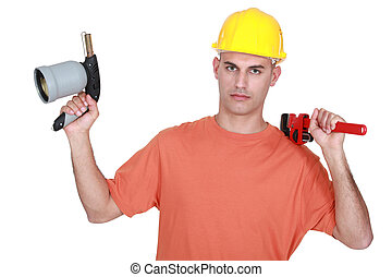 Tradesman holding a pipe wrench and a blowtorch