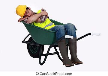 A road worker sleeping in a wheelbarrow.