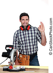 Man with circular saw making OK gesture