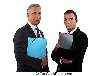 Two businessmen standing and holding files