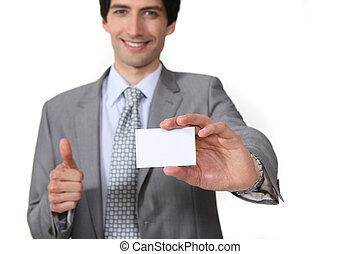 Man making thumbs-up gesture and holding business card
