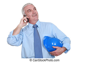 Grey-haired architect making call