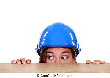 Tradeswoman peeping out from beneath a table