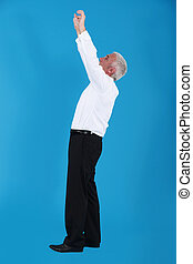 Businessman reaching up