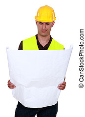 Confused tradesman looking at a technical drawing