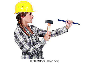 craftswoman holding a wedge and a hammer