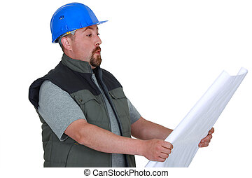 Surprised tradesman looking at a blueprint