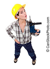 A female construction worker using a drill as a gun.