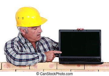 Builder pointing to laptop screen