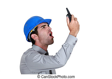 angry businessman wearing a helmet and shouting on his walkie talkie
